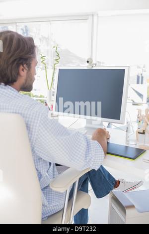 Designer seduto alla scrivania e lavorare Foto Stock