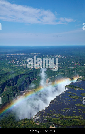 Rainbow e spray, Victoria Falls o 'Mosi-oa-Tunya' (il fumo che tuona), e il fiume Zambesi, Zimbabwe / confine Zambia Foto Stock