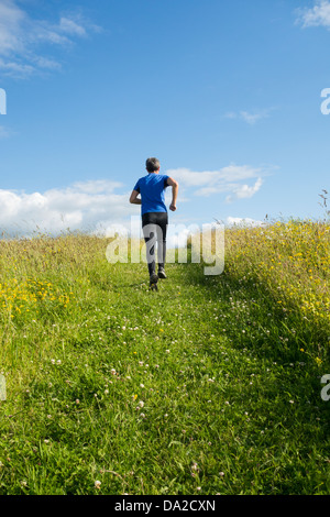 Uomo che corre in salita attraverso prati fioriti. Inghilterra, Regno Unito Foto Stock