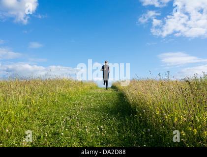 Uomo che corre attraverso il prato di fiori selvaggi. Inghilterra, Regno Unito Foto Stock