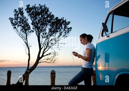 Giovane donna appoggiata sul camper van al crepuscolo Foto Stock