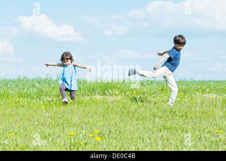 I bambini in esecuzione in campo con armi fuori Foto Stock