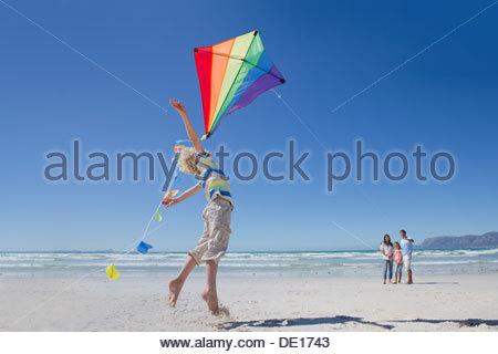Ragazzo di salto e di raggiungere per il kite di sunny beach Foto Stock