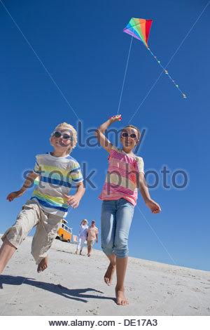 Un ragazzo e una ragazza con il kite in esecuzione su sunny beach Foto Stock