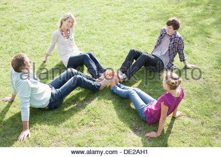 Famiglia seduto sull'erba Foto Stock