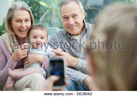 Sorridente nonni holding baby nipote e tenendo la fotografia sul telefono cellulare Foto Stock