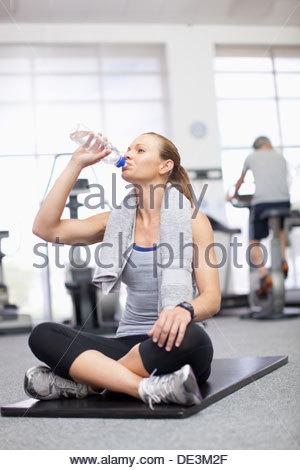 Donna con asciugamano attorno al collo di acqua potabile in palestra Foto Stock
