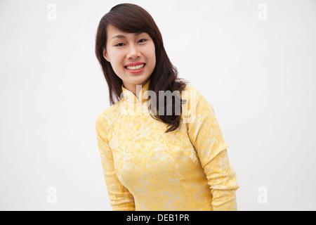 Ritratto di sorridente giovane donna che indossa un giallo abito tradizionale dal Vietnam, studio shot Foto Stock