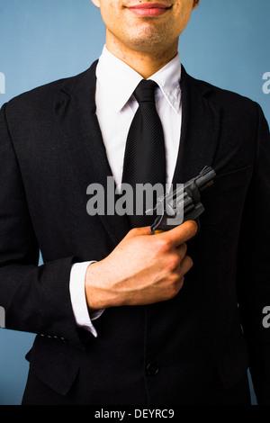 Giovane uomo in tuta è in possesso di una pistola Foto Stock