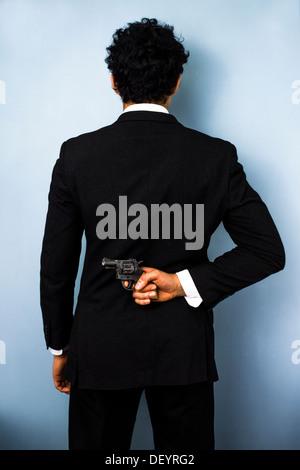 Vista posteriore di imprenditore nasconde una pistola dietro la schiena Foto Stock
