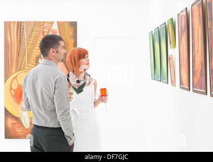 Giovane coppia caucasica in piedi in una galleria e tenuta vetri colorati di vino nelle loro mani, contemplando Foto Stock