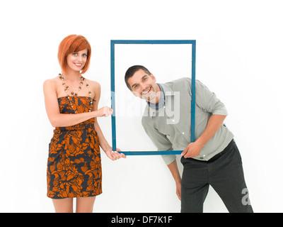 La donna caucasica tenendo un fotogramma vuoto e un uomo in posa attraverso di esso, su sfondo bianco Foto Stock