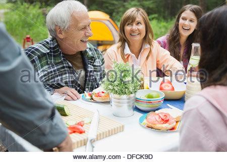 Felice coppia senior godendo di pasto con la famiglia al campeggio Foto Stock