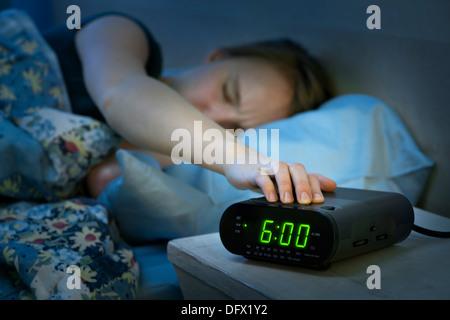 Giovane donna premendo il tasto Snooze di prima mattina digital radio sveglia Foto Stock