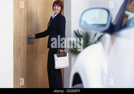 Imprenditrici di uscire di casa per il lavoro Foto Stock