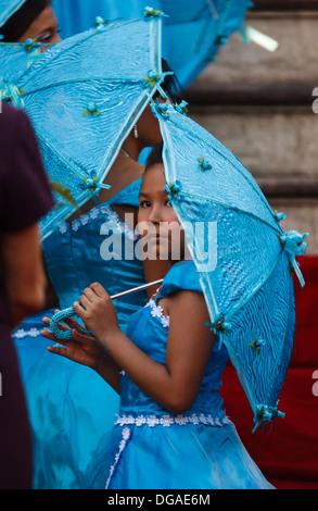 Unidentified giovane damigella in blu turchese picchi vestito da sotto ombrellone corrispondente durante il matrimonio Foto Stock