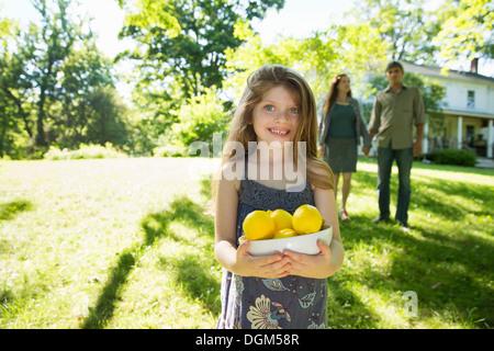 Azienda agricola. Bambini e adulti che lavorano insieme. Una ragazza con una cassa di limoni freschi frutti. Due Foto Stock
