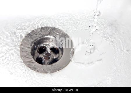 Spreco di acqua in un lavandino del bagno Foto Stock