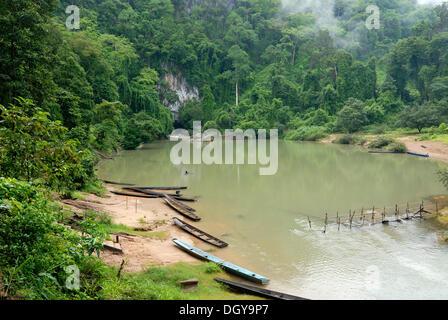 Semplice lungo le barche dei pescatori Laotiana all'ingresso del 7.5 km lungo la grotta di Tham Kong Lor, nella Foto Stock