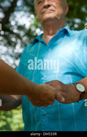 Una donna e un uomo anziano che fissano ciascuna altre mani Foto Stock