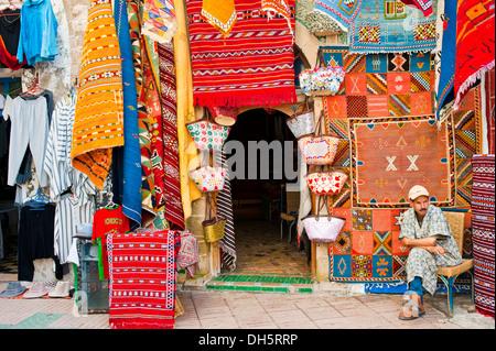 Un commerciante di tappeti seduto di fronte al suo negozio nel souk o bazaar, moquette o tappeti sono appesi alla Foto Stock