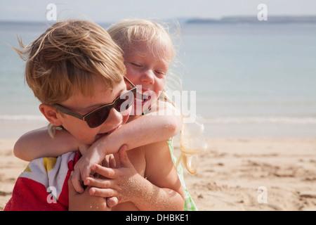 Un fratello e una sorella gioca combattimenti sulla spiaggia. Un ragazzo in occhiali da sole e una giovane ragazza Foto Stock