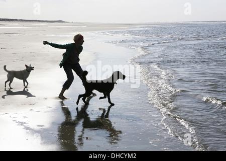 Germania, Bassa Sassonia, Frisia orientale, Langeoog, donna che gioca con i suoi cani in spiaggia Foto Stock