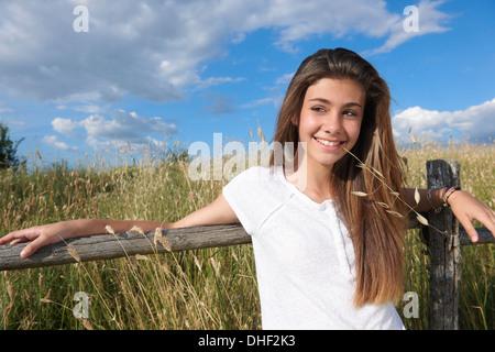 Ragazza adolescente appoggiata sulla staccionata in legno, Toscana, Italia Foto Stock