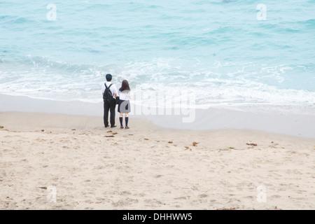 Coppia giovane tenendo le mani guardando il mare Foto Stock