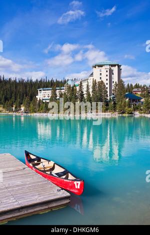 Rosso in canoa per noleggiare sul Lago Louise nella parte anteriore del Fairmont Chateau Lake Louise il Parco Nazionale Foto Stock