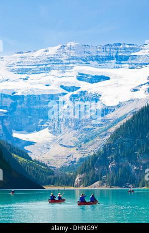 I turisti in rosso le canoe per noleggiare sul Lago Louise e il Parco Nazionale di Banff Alberta Rockies Canadesi Foto Stock