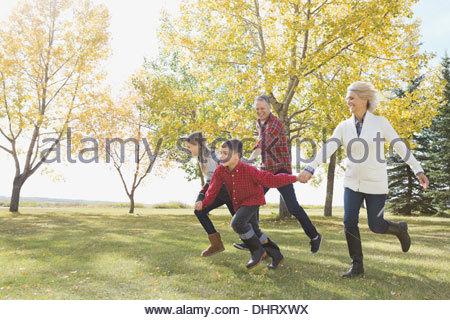 Dei bambini felici in esecuzione con i nonni all'aperto Foto Stock