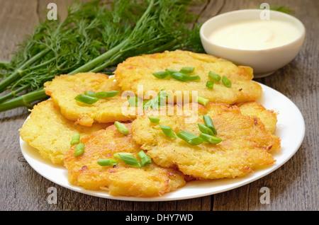 Frittelle di patate sul tavolo di legno Foto Stock