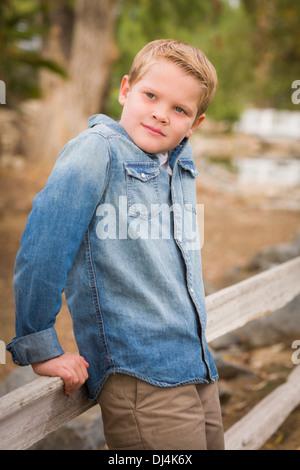 Bel giovane ragazzo appoggiata contro un recinto nel parco. Foto Stock