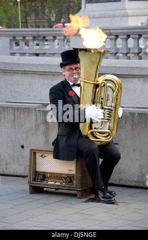 Londra, Inghilterra, Regno Unito. Busker in Trafalgar Square - riproduzione di tuba che emette fiamme Foto Stock