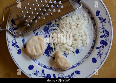 Formaggio di pecora grattugiata grossolanamente da un hand-held grattugia. Foto Stock