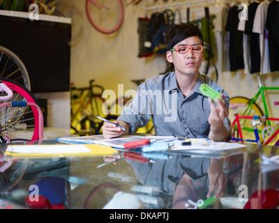 Giovane uomo esaminando parte di bicicletta in bike shop Foto Stock