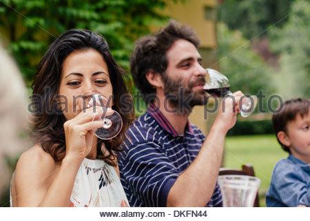 Giovane godendo di vino rosso al pasto di famiglia Foto Stock