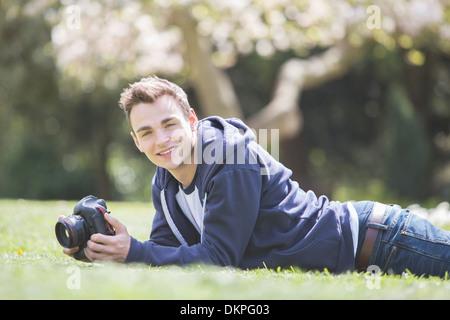 Uomo che stabilisce con la fotocamera in posizione di parcheggio Foto Stock