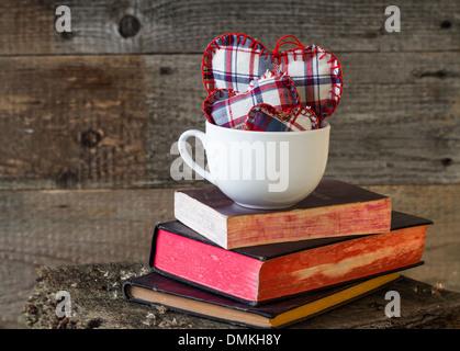 Tre cuori in una tazza bianca su libri su una tavola di legno Foto Stock