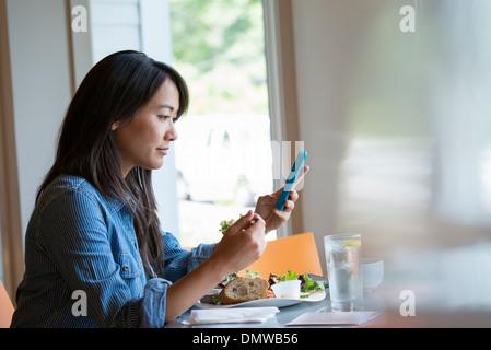 Una donna di mangiare un insalata e controllare il suo telefono. Foto Stock