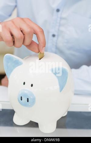 Close-up sezione intermedia di un uomo mettere moneta nel salvadanaio Foto Stock