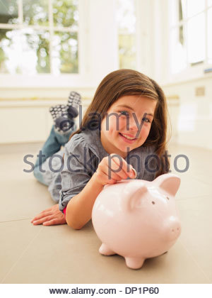 Ragazza mettendo moneta nel salvadanaio Foto Stock