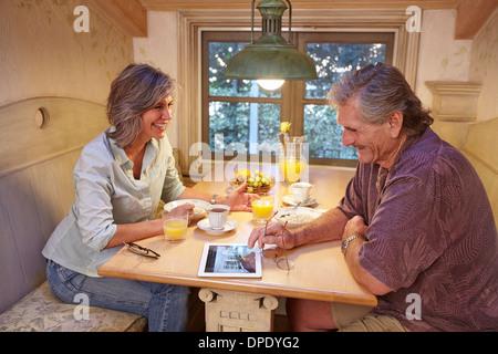 Coppia senior gustando la prima colazione e uso di tavoletta digitale Foto Stock