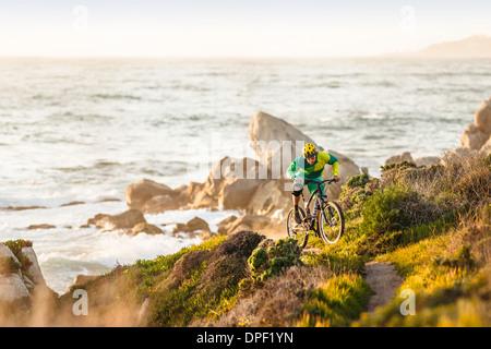 Mountain Biker nello spostamento verso l'alto sentiero costiero, Monterey Bay Area, California, Stati Uniti d'America Foto Stock