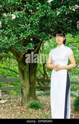 Giovane donna sorridente nel parco boschivo indossando il tradizionale abbigliamento vietnamiti. Foto Stock