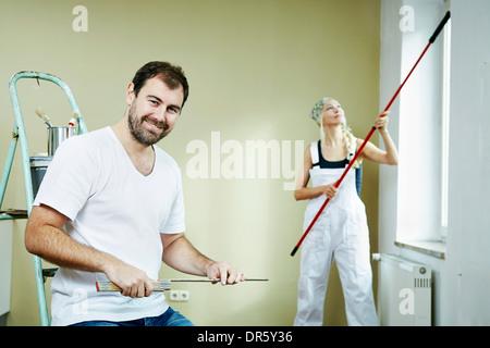 Donna pittura le pareti, uomo si siede in primo piano, Monaco di Baviera, Germania Foto Stock
