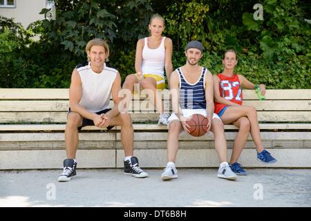 Ritratto di giocatori di basket seduto su una panchina nel parco Foto Stock