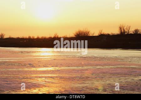 Tramonto su un lago ghiacciato Foto Stock