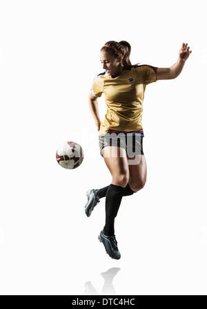 Studio shot di femmina giovane giocatore di calcio calci indietro la sfera Foto Stock